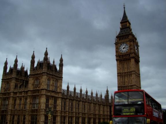 2013年7月4日に撮影したロンドンのウェストミンスター宮殿(国会議事堂)の時計塔とウェストミンスター橋を通るバスの写真