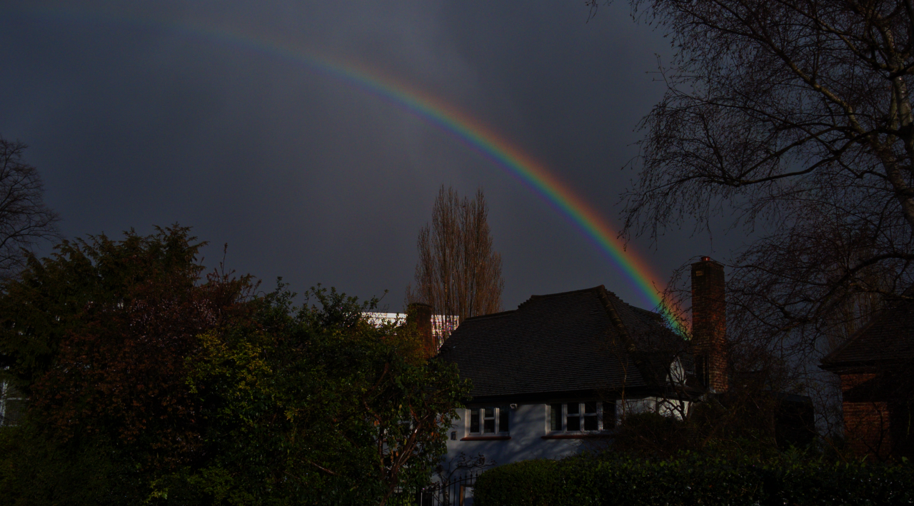 A photograph of rainbows in London, 28 March 2016: there are supernumerary bands underneath the primary rainbow and a secondary rainbow is faintly visible.