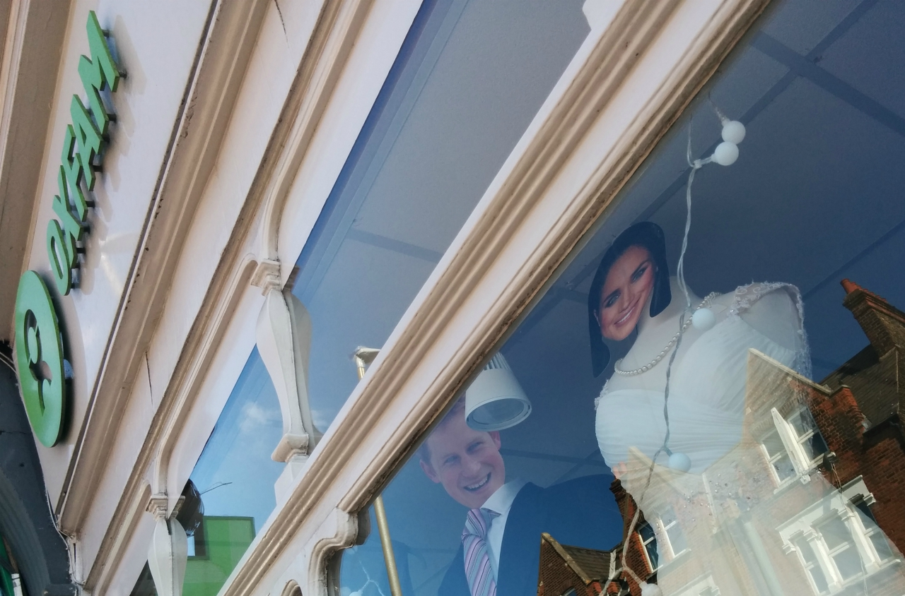The shopfront of an Oxfam charity shop in London, where mannequins in wedding attire were wearing masks of the Duke and Duchess(?) of Sussex.