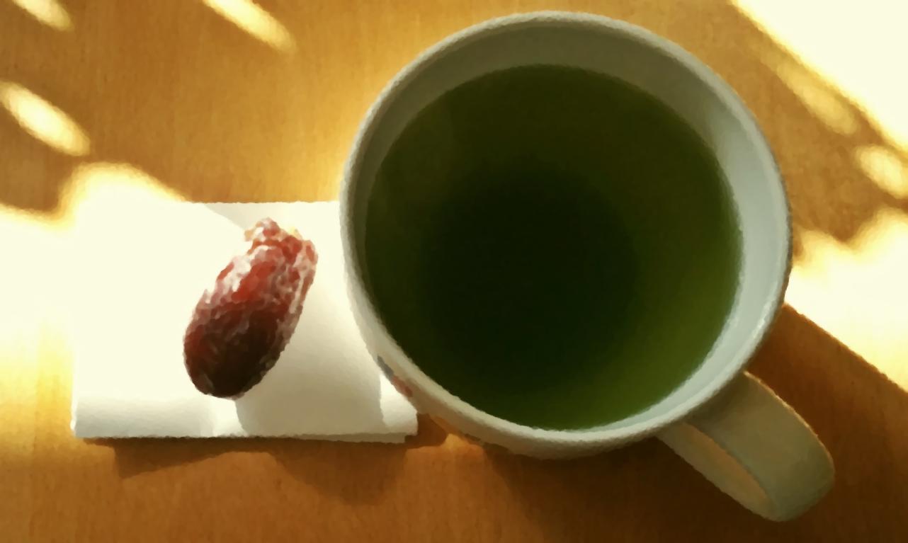 マグカップに入った緑茶とナツメヤシ