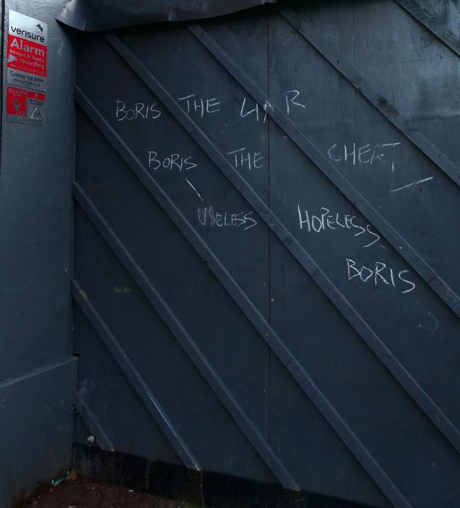 Graffiti on a boarding at a construction site: BORIS THE LIAR, BORIS THE CHEAT, USELESS HOPELESS BORIS