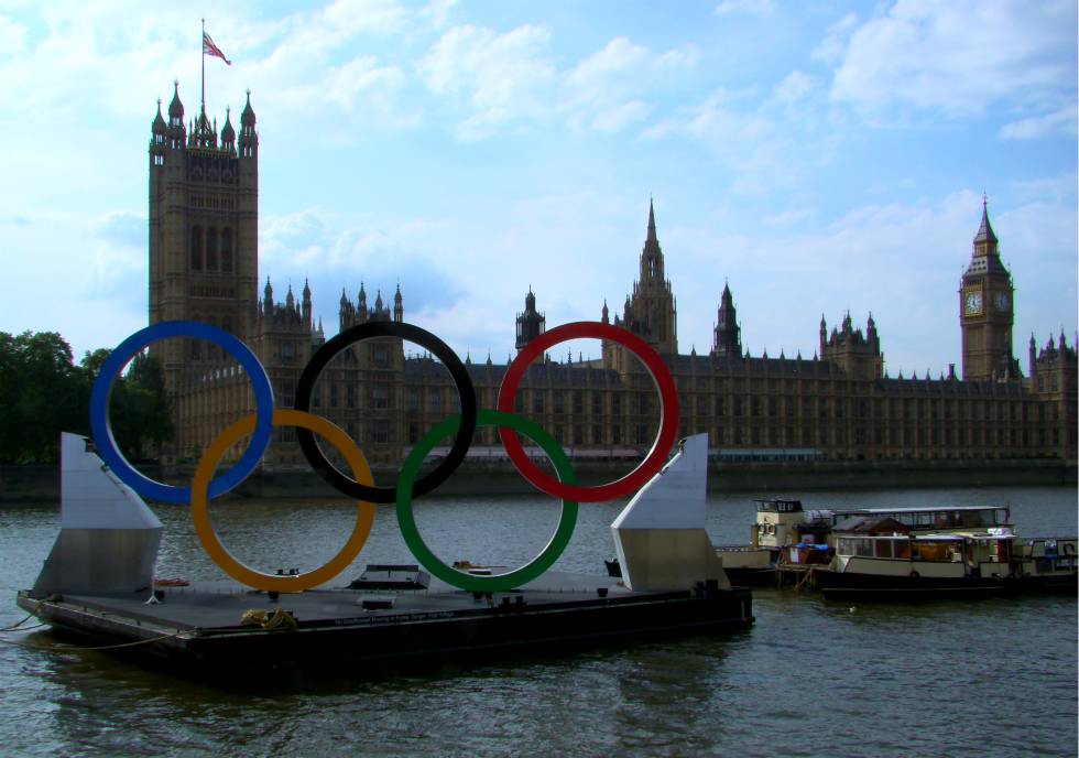 Palace of Westminster, photographed from the opposite bank of the Thames, with large Olympic rings in the foreground.