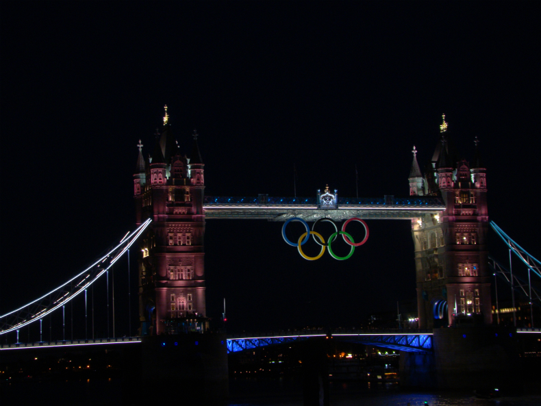 A photograph of Tower Bridge, with large Olympic rings, taken at night.